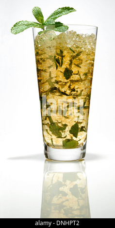 A colorful iced cocktail drink in a glass with a mint leaf garnish. - Stock Image