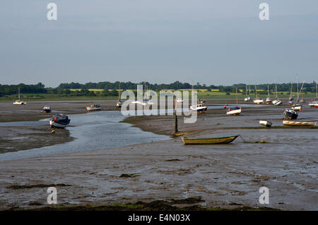 small boats resting on the mud of The River Stour aat low tide. The far shore is Suffolk - Stock Image