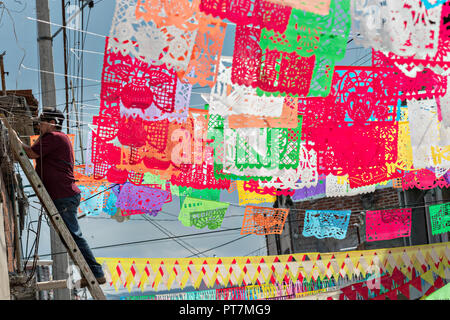 Residents hand Mexican papel picado banners in preparation for the 8th Night Celebration marking the end of the Feast of St Michael in the central Mexican town of Uriangato, Guanajuato. Every year the town decorates 5km of road with religious icons made from colored sawdust and flowers in preparation for the statue of the patron saint to be paraded through the town. Uriangato became an international sensation after wowing Brussels with their floral carpet displayed at the Brussels Grand-Place during the Belgium Floral Carpet festival. - Stock Image