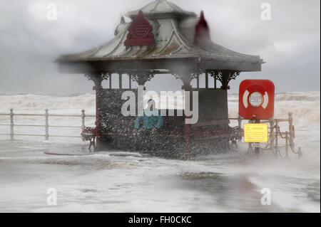 Storm on the old  Blackpool south central shore sea front.  Male sheltering in a pagoda type shelter - Stock Image