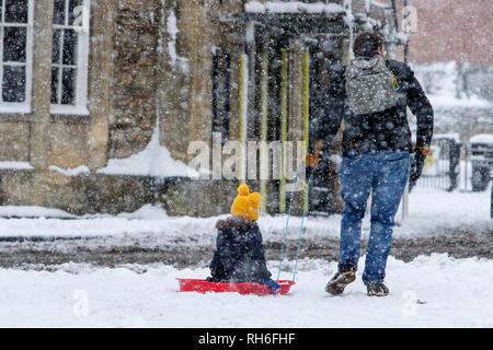 Chippenham, Wiltshire, UK. 1st February, 2019. A man is pictured pulling a child on a sledge in Chippenham town centre as Southern England experiences heavy snow showers . Credit: Lynchpics/Alamy Live News - Stock Image