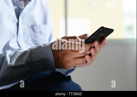 man holding en hands and using digital tablet  Mobile Phone telephone with blank copy space scree - Stock Image