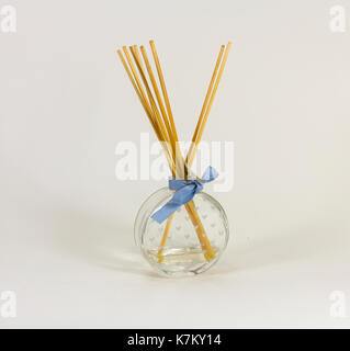 Reed fragrance diffuser, glass flask with heart motif markings and blue ribbon round the neck. Ratten reed sticks gradually diffuse scent. - Stock Image