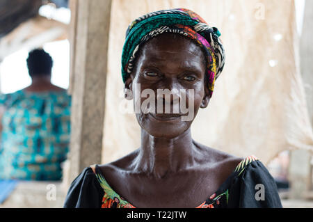 Adzopé, côte d'ivoire - June 10, 2017: Portrait of a  old woman in a camisole and her head tied by a piece of loincloth looks at the camera - Stock Image