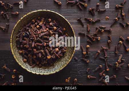 Brass Bowl of Cloves on Wood Table - Stock Image