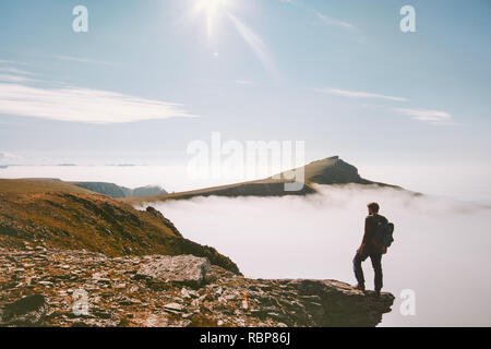 Traveler man hiking alone in mountains over clouds enjoying view active summer vacations trip adventure travel lifestyle outdoor - Stock Image