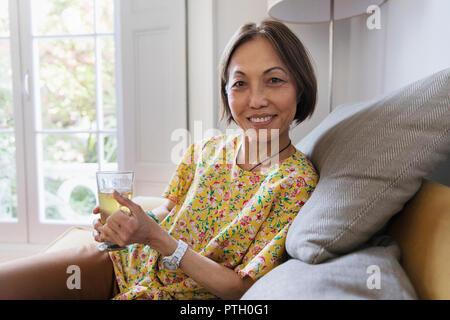 Portrait confident senior woman drinking tea in living room - Stock Image