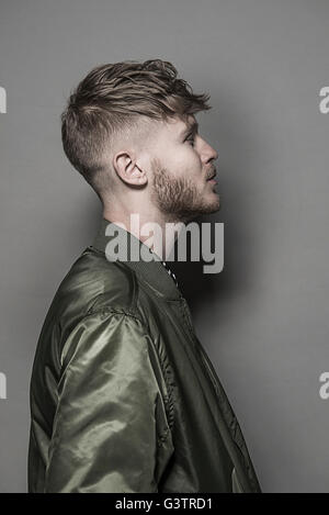 Studio portrait of a bearded young man wearing a green bomber jacket. - Stock Image