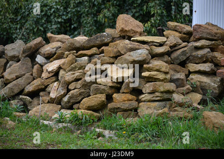 Pile of ironstone whcih had been part of a wall in the north Oxfordshire village of Hook Norton - Stock Image