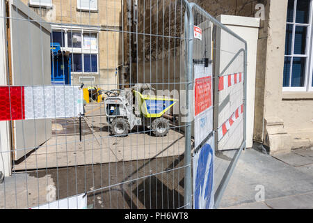 Mini dumper truck behind safety fencing outside of property being renovated in the City of Bath - Stock Image