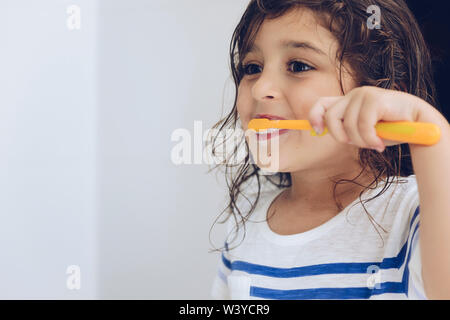 portrait of a little girl brushing her teeth in the bathroom before going to bed after shower, kids hygiene concept, copy space for text - Stock Image