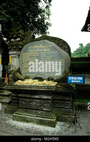 Offerings on carved stone entrance Bahasa Bali Balinese Script Pura Tirtha Empul temple sacred springs Bali Indonesia - Stock Image