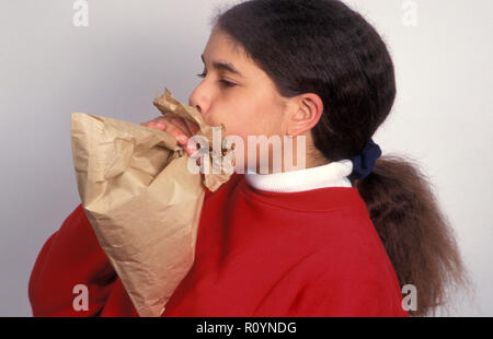 asthmatic young girl blowing into brown paper bag - Stock Image