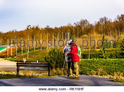 Poznan, Poland - February 10, 2019: Elderly couple standing with hiking sticks next to a wooden bench having a break at the Malta park on a cloudy day - Stock Image