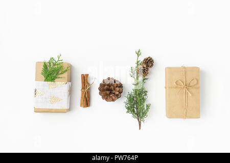 Gift boxes wrapped in craft paper tied with twine fabric ribbon pine cones juniper cinnamon on solid white background. New Year presents holiday prepa - Stock Image