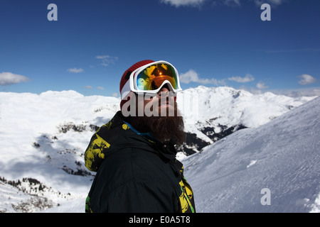 Mid adult man skier looking up at mountain, Mayrhofen, Tyrol, Austria - Stock Image