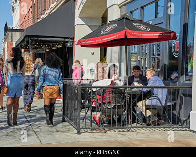 Group of teens or teenagers eating at a sidewalk cafe, Jimmy Johns restaurant or sandwich shop in Montgomery Alabama, USA. - Stock Image