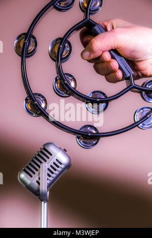 Man's hand holding a D-shaped tambourine with a plastic frame and metal jingles (zills), positioned in front of - Stock Image