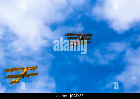 Flying triplane Fokker Dr-1 M and biplane Tiger Moth I-GATO replicas next to each other between the clouds. - Stock Image