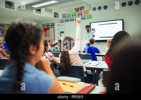 Junior high school student raising hand, asking a question during lesson in classroom - Stock Image