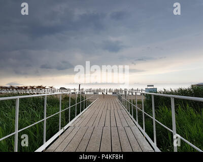 Wooden bridge as trail to the beach in a cloudy summer day before rain. - Stock Image