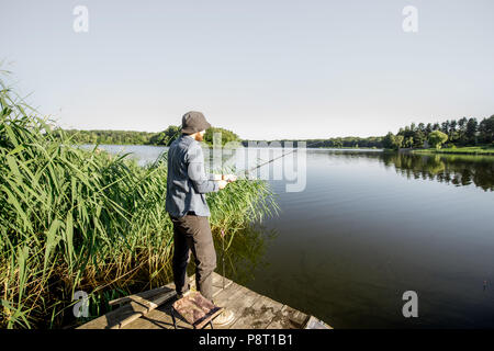 Fishermen catching fish with fishing rod standing on the pier near the beautiful lake in the morning - Stock Image