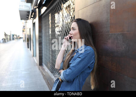 Serious woman talks on smart phone leaning in a wall in the street - Stock Image