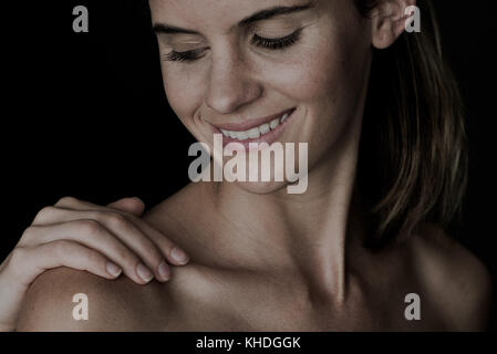 Hand touching young woman's bare shoulder - Stock Image