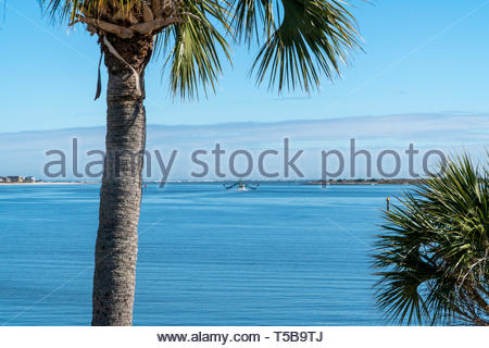 A shrimp boat approaches the mouth of Matanzas Bay, viewed from the Castillo de San Marcos, a Spanish fortification at St. Augustine, Florida USA - Stock Image