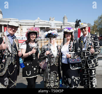 London, UK. 20th Apr, 2019. Pearly Kings and Queens pose for photos as preparations get underway for The Feast of St George in Trafalgar Square, London. Glorious sunshine adds to the English Country Garden feel as the hottest Easter in over 70 years is predicted. Credit: Keith Larby/Alamy Live News - Stock Image