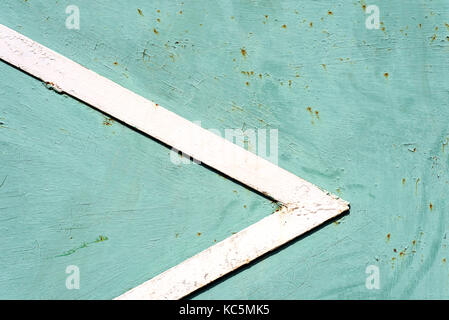 White painted metal triangle edge creating a pointer on a fading green metallic background - Stock Image