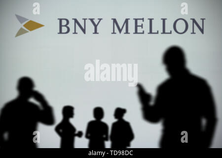 The BNY Mellon logo is seen on an LED screen in the background while a silhouetted person uses a smartphone in the foreground (Editorial use only) - Stock Image