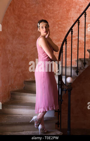 Beautiful woman in authentic retro twenties flapper dress and headband walking down an antique spiral staircase - Stock Image