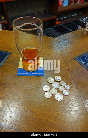 Nearly empty beer glass on bar counter with coins for another pint - Stock Image
