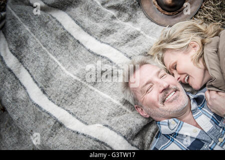 Senior couple cuddling together on a blanket at their campsite. - Stock Image
