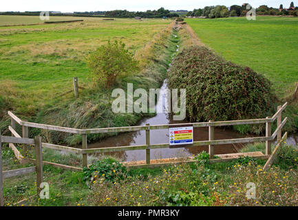 A land drainage ditch meeting the Norfolk Coast Path for discharge into the Creek at Morston, Norfolk, England, United Kingdom, Europe. - Stock Image