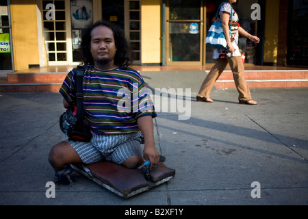 A physically handicapped Filipino begs for money on the street in Makati City, Manila, Philippines. - Stock Image