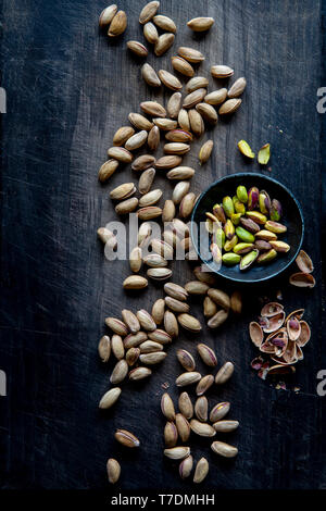 Pistachios and nutshells over black wooden background with copy space - Stock Image