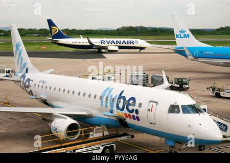 Flybe, Ryanair and KLM passenger plane jet aircraft airplane on runway apron seen from boarding gates of Manchester Airport Terminal Building, England - Stock Image