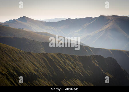 Fog in the mountains, several mountain ranges with a grey sky on the horizon - Stock Image
