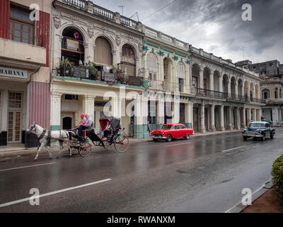 Old American cars and a horse and carriage on wet streets of Paseo de Marti after a rain storm in central Havana, Cuba - Stock Image