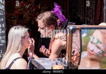 A festival goer gets her face painted at Latitude Festival 2018. - Stock Image