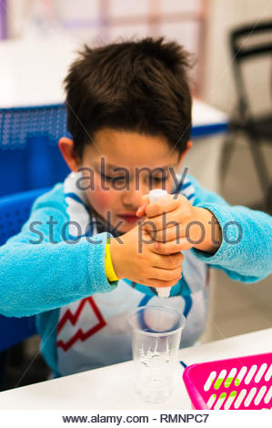 Poznan, Poland - February 2, 2019: Young boy squeezing glue in a plastic cup during experiments in a university open day. - Stock Image