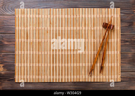 two sushi chopsticks with empty brown bamboo mat or wood plate on wooden Background Top view with copy space. empty asian food background. - Stock Image