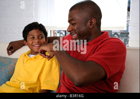 African American father and son having a light-hearted conversation - Stock Image