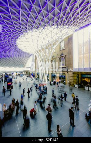 The concourse and elaborate roof of Kings Cross train station with commuters, passengers and travellers waiting for trains - Stock Image