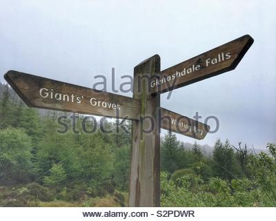 A signpost on the Isle of Arran, Scotland, giving directions to Giants' Graves, Glenashdale Falls and Whiting Bay. - Stock Image