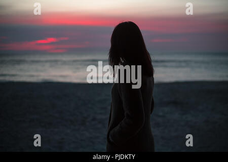 Young woman standing alone on beach, watching sunrise, rear view - Stock Image