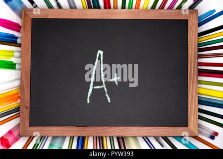 Education concept. A with plus or perfect mark written on blackboard, chalkboard - Stock Image