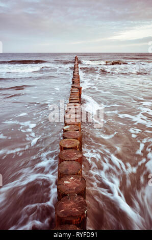 Wooden breakwater at sunrise, long exposure picture, color toning applied. - Stock Image